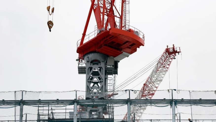 Workers construct a building in Tokyo Wednesday, June 8, 2016. Japan has revised upward its estimate of growth in the first quarter of this year, thanks to smaller drop in business investment than reported earlier. (AP Photo/Eugene Hoshiko)