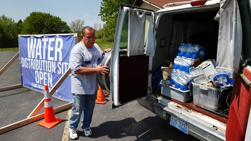 In this Wednesday, May 25, 2016 photo, Raul Garcia Jr., loads water into a van at Our Lady of Guadalupe Church in Flint, Mich. Officials with Our Lady of Guadalupe recognized the language and cultural barriers in January, when they started distributing supplies as well as information in English and Spanish developed with the help of government officials. (AP Photo/Paul Sancya)