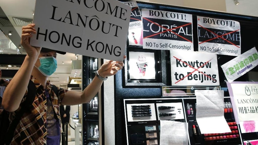 A protestor displays a placard at a Lancome counter inside a department store at Hong Kong's Times Square, Wednesday, June 8, 2016. French cosmetics company Lancome has sparked a backlash in Hong Kong after it canceled a promotional concert featuring a singer known for pro-democracy views, with many accusing it of caving in to political pressure from Beijing. (AP Photo/Kin Cheung)