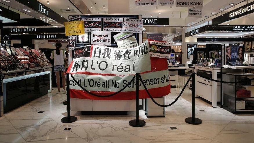 "Banner and placards are displayed by protesters at a Lancome counter inside a department store at Hong Kong's Times Square, Wednesday, June 8, 2016. French cosmetics company Lancome has sparked a backlash in Hong Kong after it canceled a promotional concert featuring a singer known for pro-democracy views, with many accusing it of caving to political pressure from Beijing. The placard reads: ""Shame on self-sensorship"".  (AP Photo/Kin Cheung)"