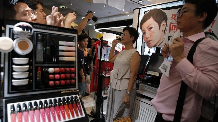 Protestors display placards and the picture of local singer Denise Ho at a Lancome counter inside a department store at Hong Kong's Times Square, Wednesday, June 8, 2016. French cosmetics company Lancome has sparked a backlash in Hong Kong after it canceled a promotional concert featuring a singer known for pro-democracy views, with many accusing it of caving to political pressure from Beijing. (AP Photo/Kin Cheung)
