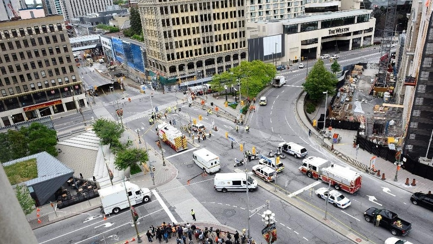 People look on at a large sinkhole that formed on Rideau Street on Wednesday, June 8, 2016, in Ottawa. A mall and buildings around a major intersection near Parliament have been evacuated because of the sinkhole. The city of Ottawa said in a statement Wednesday the road collapse occurred at Rideau Street and Sussex Drive, not far east of Parliament. A van fell into the sinkhole but there are no reports of injuries. The city says buildings in the area have been evacuated due to the smell of gas.  (Justin Tang/The Canadian Press via AP)