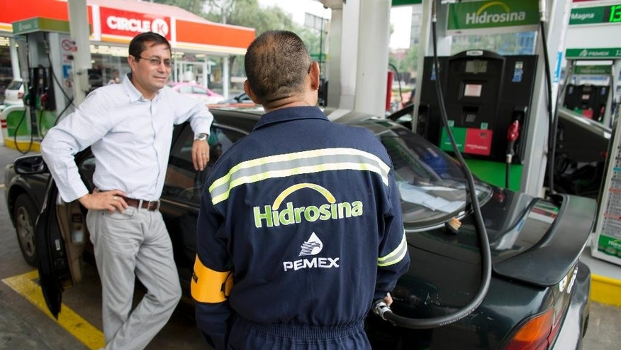 A Hidrosina pumps gas for a customer in Mexico City, Tuesday, June 7, 2016. Mexico's ubiquitous Pemex gas stations now have competition along the country's highways and city streets for the first time in nearly eight decades. Two companies have collectively opened three gas stations under their own brands, breaking one of the state-owned petroleum company's last monopolies. Opening the retail sector to competition was part of energy reforms passed in 2014. (AP Photo/Eduardo Verdugo)