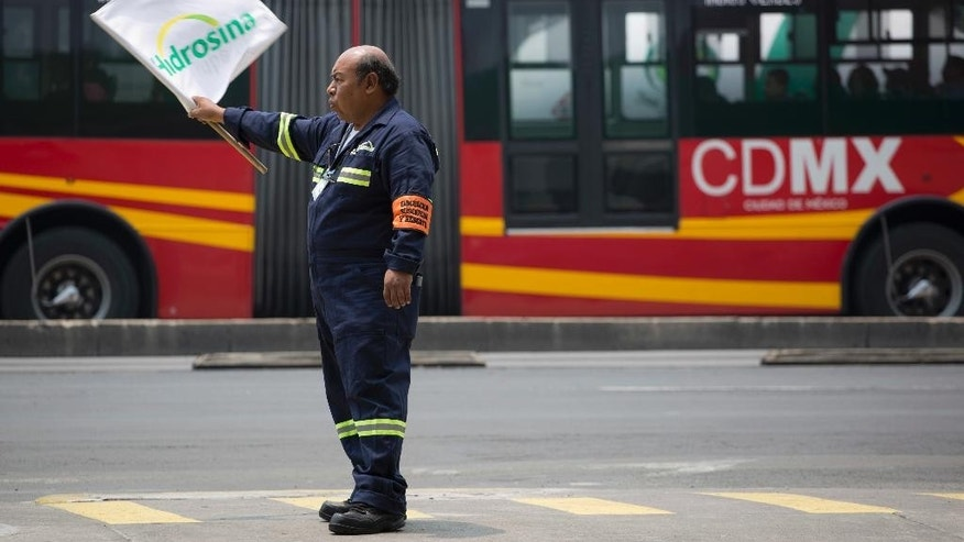 An employee of a Hidrosina gas station waves a banner to attract customers, in Mexico City, Tuesday, June 7, 2016. Mexico's ubiquitous Pemex gas stations now have competition along the country's highways and city streets for the first time in nearly eight decades. Two companies have collectively opened three gas stations under their own brands, breaking one of the state-owned petroleum company's last monopolies. Opening the retail sector to competition was part of energy reforms passed in 2014. (AP Photo/Eduardo Verdugo)