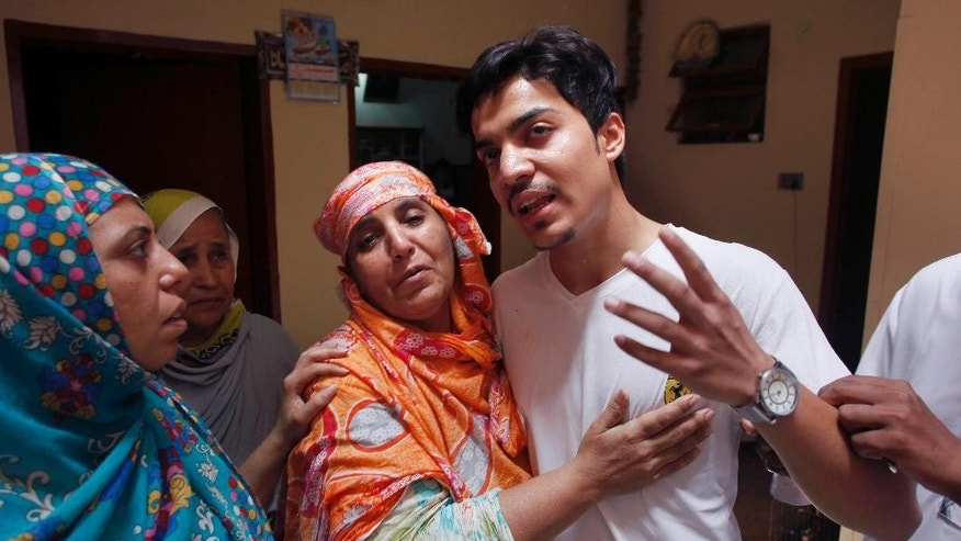 Family members comfort Hassan Khan, center, the husband of Zeenat Rafiq, who was burned alive, allegedly by her mother, at his home in Lahore, Pakistan Wednesday, June 8, 2016. A Pakistani woman was arrested Wednesday after dousing her daughter with kerosene and burning her alive, allegedly because the girl had defied her family to marry a man she was in love with, police said. (AP Photo/K.M. Chaudary)