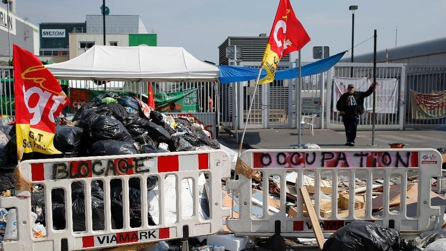 French striking CGT labour Union garbage collectors block access with pile of rubbish bags to the Paris' waste treatment center in Ivry Sur Seine, near Paris, France, Wednesday June 8, 2016. After a rough couple of months which have included protests, fuel shortages, rail strikes and once-in-a-generation floods, France's capital is facing a new challenge : Piles of uncollected trash. A new wave of strikes is disrupting trash collection in Paris with only two days to go until the European Championship soccer tournament, a sporting event predicted to draw 2.5 million spectators. (AP Photo/Francois Mori)