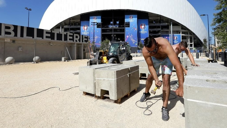 Labourer work in front of the Velodrome Stadium, in Marseille, southern France, Wednesday, June 8, 2016. France has revamped its stadiums for the biggest-ever European Championship, which begins Friday when the host nation takes on Romania at the Stade de France in the Paris suburb of Saint-Denis. (AP Photo/Claude Paris)