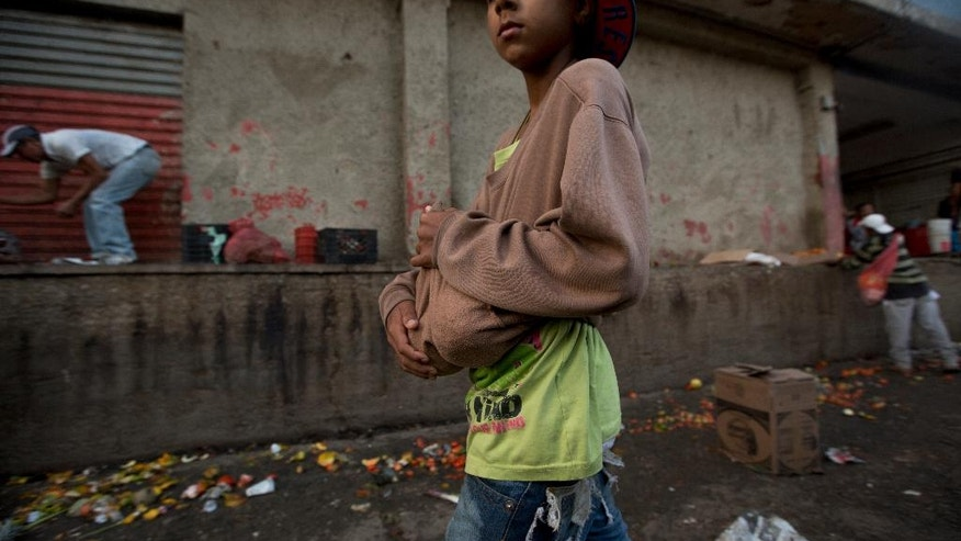 In this June 3, 2016 photo, a boy carries two pineapples he found in the trash area of the Coche public market in Caracas, Venezuela. Staples such as corn flour and cooking oil are subsidized, costing pennies at the strongest of two official exchange rates. But fruit and vegetables have become an unaffordable luxury for many Venezuelan families. (AP Photo/Fernando Llano)