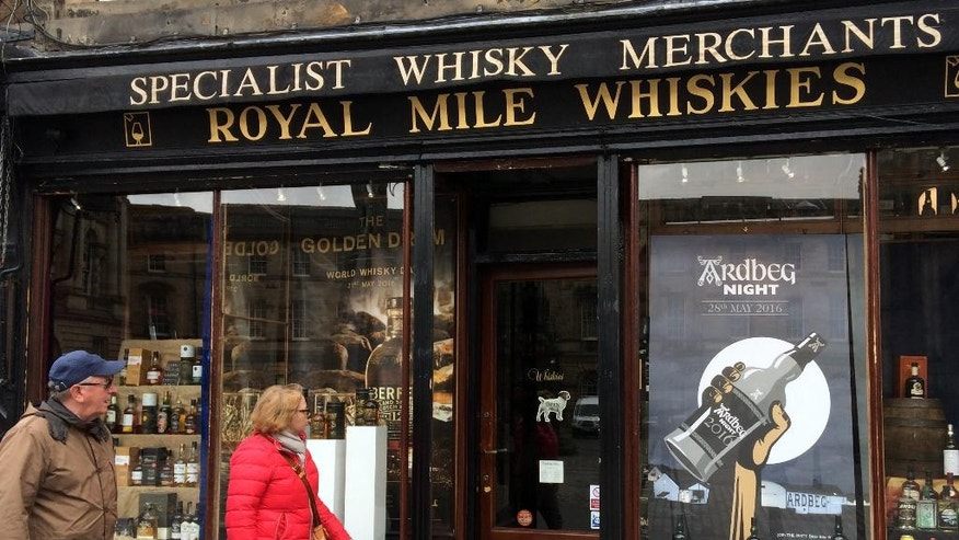 "In this picture taken on Saturday, May 28, 2016, a man and a woman pass a whisky shop on the ""Royal mile"" in Edinburgh, Scotland. Scotch Whisky Distillers, small and large, are very supportive of the UK's membership of the European Union. Scotch Whisky is Scotland's biggest export, supporting about 40,000 jobs in Scotland. (AP Photo/ Dorothee Thiesing)"