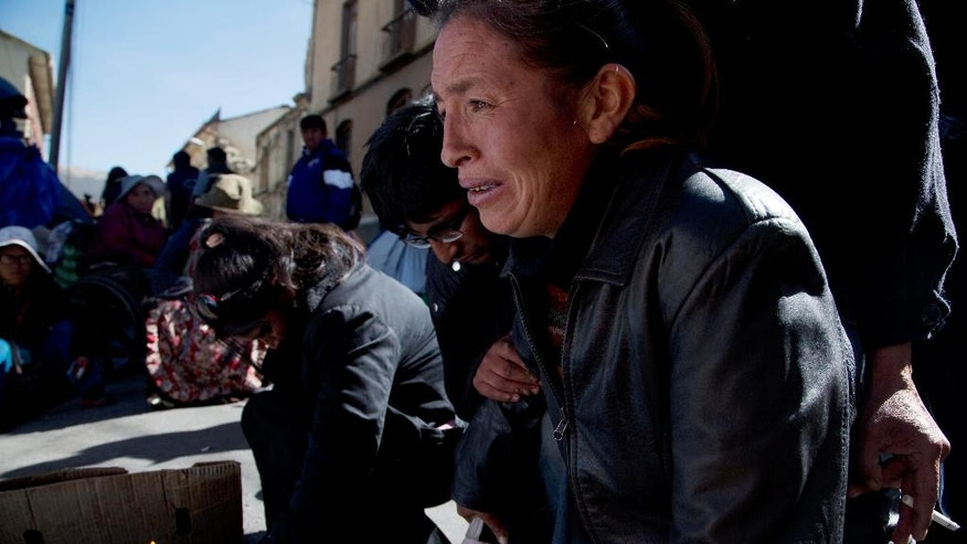 A woman cries in front of two mock coffins, symbolizing protesters with disabilities who died last night, in La Paz, Bolivia, Thursday, June 9, 2016. The two protesters were run over by a drunk driver as they slept in their encampment in Cochabamba, one of many cities where disabled people are carrying out an ongoing protest to demand an increase in state disability compensaiton, from the annual 1,000 Bolivianos, to a monthly stipend of 500, or about $73 dollars. (AP Photo/Juan Karita)