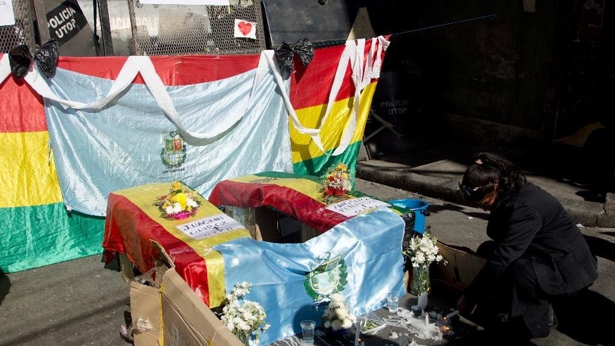 A disabled woman lights a candle before two mock coffins, symbolizing protesters with disabilities who died last night, in La Paz, Bolivia, Thursday, June 9, 2016. The two protesters were run over by a drunk driver as they slept in their encampment in Cochabamba, one of many cities where disabled people are carrying out an ongoing protest to demand an increase in state benefits, from the annual 1,000 Bolivianos, to a monthly stipend of 500, or about $73 dollars. (AP Photo/Juan Karita)