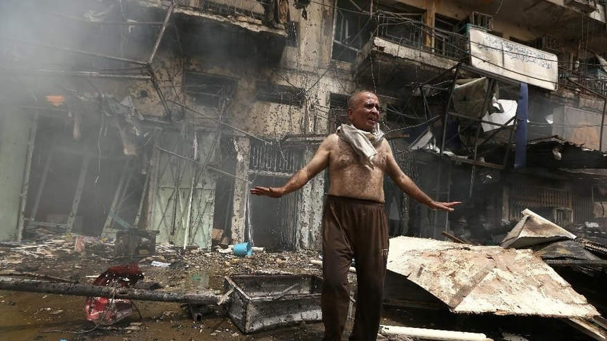 A survivor looks for his family members at the scene of a deadly suicide car bomb attack in the New Baghdad neighborhood of Baghdad, Iraq, Thursday, June 9, 2016. Two separate suicide attacks in and outside the Iraqi capital have killed at least 27 people and wounded dozens. Officials say the deadliest bombing took place in New Baghdad, a commercial area of a majority Shiite neighborhood in Baghdad, killing over a dozen civilians. Another suicide bomber rammed his explosives-laden car into an Iraqi army checkpoint north of Baghdad, killing at least 12 people. (AP Photo/Hadi Mizban)