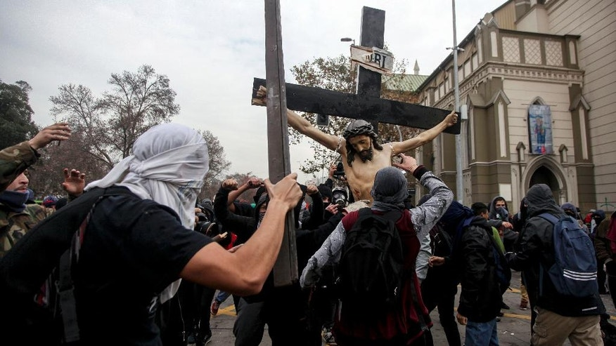A group of masked men carry a statue of a crucified Christ after taking it out of a church that they looted in the Chilean capital in Santiago, Chile, Thursday, June 9, 2016. The Roman Catholic church was desecrated during a student protest in Santiago held on Thursday. Vandals broke into the church and destroyed a the statue of the crucified Christ before they took off with other religious iconography.  Student marches in Chile are usually peaceful but often end with clashes between police in riot gear and groups of vandals who loot shops and hurl rocks and Molotov cocktails. (AP Photo/Felix Marquez)