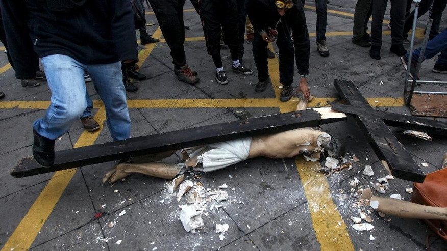 A group of masked men stand around a crucified Christ they destroyed after taking it out of a church that they looted in the Chilean capital in Santiago, Chile, Thursday, June 9, 2016. The Roman Catholic church was desecrated during a student protest in Santiago held on Thursday. Vandals broke into the church and destroyed a the statue of the crucified Christ before they took off with other religious iconography.  Student marches in Chile are usually peaceful but often end with clashes between police in riot gear and groups of vandals who loot shops and hurl rocks and Molotov cocktails. (AP Photo/Felix Marquez)