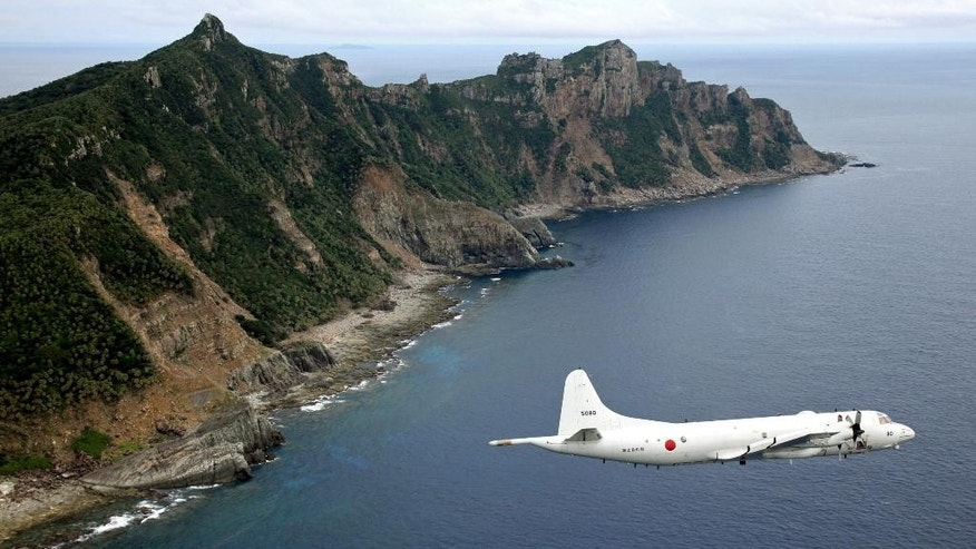 FILE - In this Oct. 13, 2011 file photo, Japan Maritime Self-Defense Force P-3C Orion surveillance plane flies over the disputed islands, called the Senkaku in Japan and Diaoyu in China, in the East China Sea.  Japan protested to China on Thursday, June 9, 2016,  after spotting a Chinese warship for the first time near disputed islands in the East China Sea.  Japanese officials said a Chinese navy frigate was seen off the coast of the Japanese-controlled Senkaku islands, also claimed by China and called the Diaoyu islands. The ship did not violate Japan's territorial waters, and it has since left the area.(Kyodo News via AP, File) JAPAN OUT, CREDIT MANDATORY
