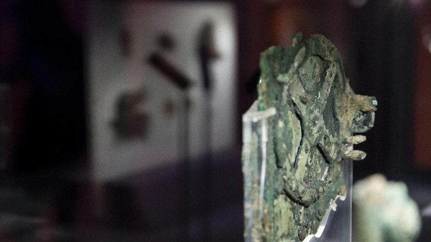 A fragment of the 2,100-year-old Antikythera Mechanism, believed to be the earliest surviving mechanical computing device, is displayed at the National Archaeological Museum, in Athens, Thursday, June 9 , 2016. An international team of scientists says a decade's painstaking work on the corroded fragments found in an ancient Greek shipwreck has deciphered roughly 500 words of text that explained the workings of the complex machine, described as the world;s first mechanical computer. (AP Photo/Petros Giannakouris)