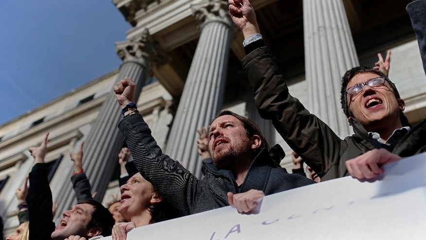 FILE - In this Jan. 13, 2016 file photo, Spanish Podemos party leader Pablo Iglesias, second right, shouts slogans as he poses for the media with his party members outside the Spanish parliament in Madrid, Spain. Spain's political parties are set to launch two-week campaigns leading up to a June 26, 2016 election aimed at breaking six months of political paralysis after a December election shattered the nation's two traditional two-party system and politicians failed to negotiate a governing coalition. Campaigning begins at midnight Friday. (AP Photo/Francisco Seco, File)