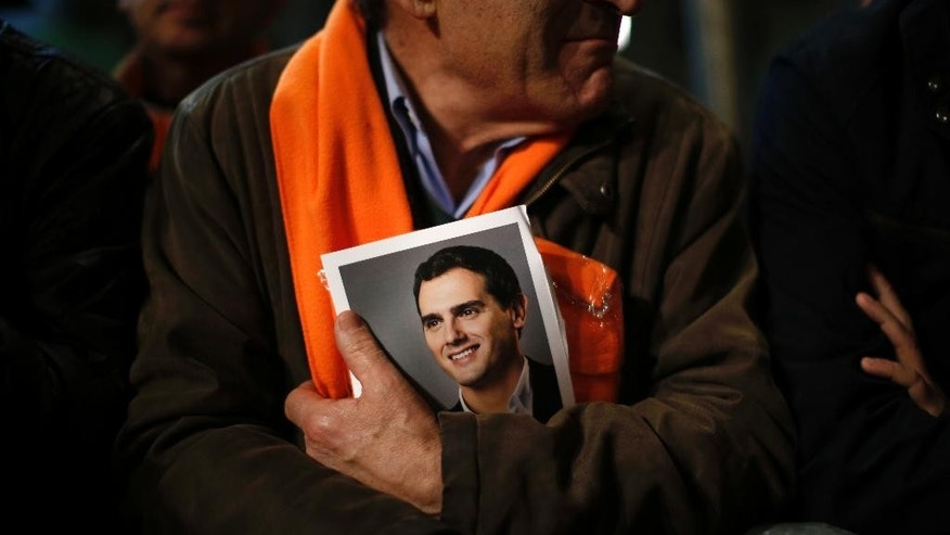 FILE - In this Dec. 18, 2015 file photo, a man holds a photo of Ciudadanos party leader Albert Rivera before the closing campaign rally in Madrid, Spain. Spain's political parties are set to launch two-week campaigns leading up to a June 26, 2016 election aimed at breaking six months of political paralysis after a December election shattered the nation's two traditional two-party system and politicians failed to negotiate a governing coalition. Campaigning begins at midnight Friday. (AP Photo/Emilio Morenatti, File)