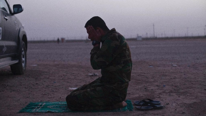 FILE - In this Tuesday, June 7, 2016 file photo, an Iraqi policeman from Anbar province prays after breaking his Ramadan fast at Camp Tariq outside Fallujah, Iraq, Tuesday, June 7, 2016. The fight to retake the Islamic State-held city of Fallujah is continuing into Ramadan, and both sides say the Muslim holy month gives their military cause a greater significance. While Iraq's most influential Shiite cleric says fighters do not need to fast if they believe it will compromise their abilities on the battlefield, many Iraqi troops say they plan to so despite the harsh conditions and the summer heat. (AP Photo/Maya Alleruzzo, File)