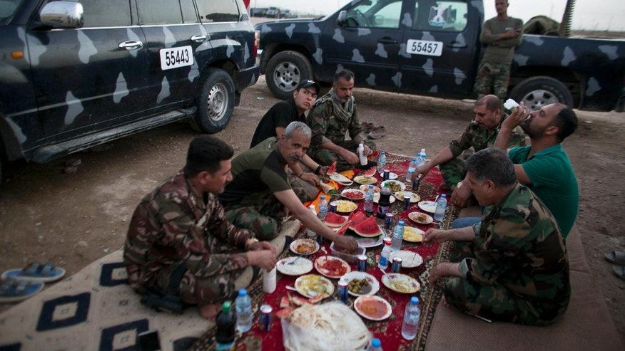 FILE - In this Tuesday, June 7, 2016 file photo, policemen from Anbar province and Iraqi journalists break their Ramadan fast together at Camp Tariq outside Fallujah, Iraq. The fight to retake the Islamic State-held city of Fallujah is continuing into Ramadan, and both sides say the Muslim holy month gives their military cause a greater significance. While Iraq's most influential Shiite cleric says fighters do not need to fast if they believe it will compromise their abilities on the battlefield, many Iraqi troops say they plan to so despite the harsh conditions and the summer heat.(AP Photo/Maya Alleruzzo, File)