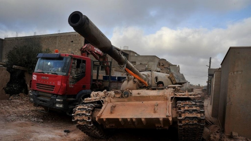 "FILE - In this March 7, 2016 file photo, a man loyal to the Libyan armed forces sits in a tank during clashes with Islamic State group militants west of Benghazi, Libya. Islamic State militants are fleeing their main bastion in Libya, a day after militiamen loyal to a U.N.-brokered government pushed into the central city of Sirte. Some militants have reportedly shaved off their beards to escape. The capture of Sirte capped an almost month-long effort by the militiamen to take the IS stronghold. The fighters, mostly from the western Libyan city of Misrata, have also dismantled a ""stage of horror"" in the city center that was used by IS for public beheadings. (AP Photo/Mohammed el-Shaiky, File)"