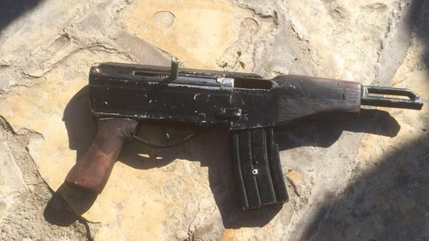 "This undated photo provided by the Israeli Police shows a handmade gun produced in the West Bank. Welded together from spare gun parts and pipes, the gun looks like a handgun but with an extended barrel and a long magazine of bullets. The weapon, known by its street name ""Carlo,"" was used by Palestinian gunmen to kill four people and wound five others in Tel Aviv on Wednesday night as well as several other attacks since the current round of violence erupted in September. (Israeli Police via AP)"