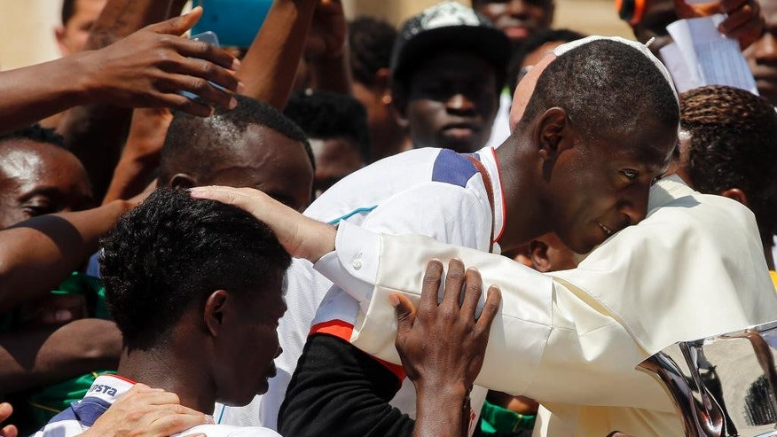 Pope Francis is hugged by migrants of the San Francesco association at the end of his weekly general audience in St. Peter's Square at the Vatican, Wednesday, June 8, 2016. (AP Photo/Fabio Frustaci)