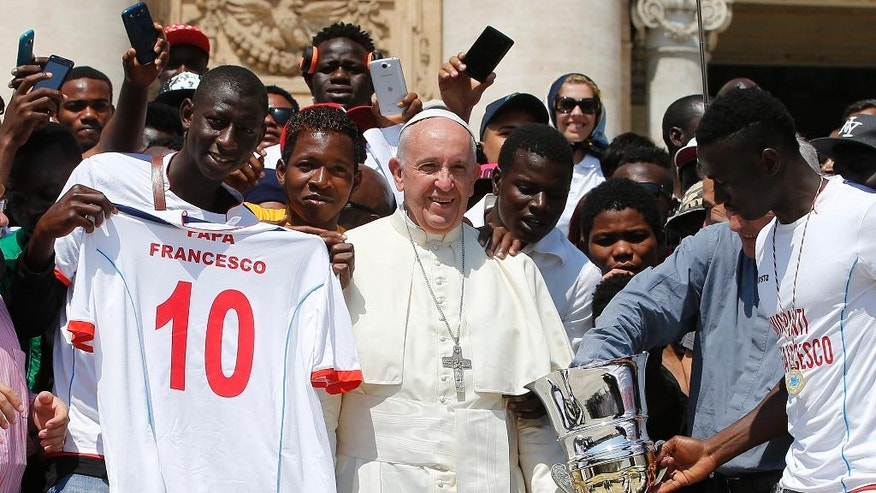 Pope Francis poses for a family picture with migrants of the San Francesco association at the end of his weekly general audience in St. Peter's Square at the Vatican, Wednesday, June 8, 2016. (AP Photo/Fabio Frustaci)