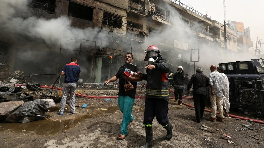 Iraqi firefighters help survivors at the site of a deadly suicide car bomb attack in the neighborhood of New Baghdad, Iraq, Thursday, June 9, 2016. Two separate suicide attacks in and outside the Iraqi capital have killed at least 27 people and wounded dozens. Officials say the deadliest bombing took place in New Baghdad, a commercial area of a majority Shiite neighborhood, killing over a dozen civilians. Another suicide bomber rammed his explosives-laden car into an Iraqi army checkpoint north of Baghdad, killing at least 12 people. (AP Photo/Hadi Mizban)