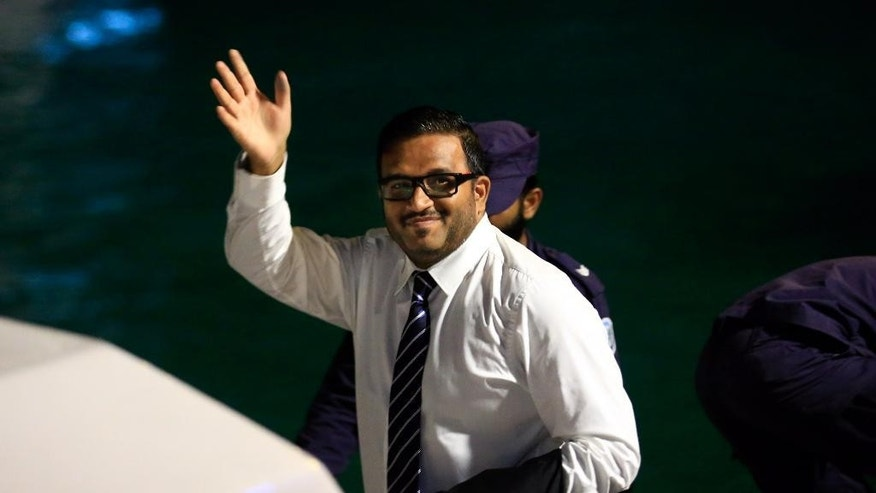 Former Maldives vice president Ahmed Adeeb waves to the media before he boards a police speed boat in Maldives, early Friday, June 10, 2015. A Maldives court on Thursday convicted the country's former vice president of masterminding a plot to kill the president by exploding a bomb on his speedboat last year and sentenced him to 15 years in prison. (AP Photo/Sinan Hussain)