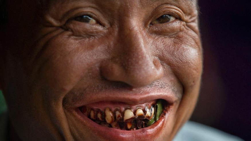 """In this Friday, June 3, 2016 photo, a habitual """" kun-ya"""" eater with some betel leaves in his mouth smiles in Yangon, Myanmar. Chewing """"kun-ya"""" as vital to life in Myanmar as cheese is to France or tea to Britain. For millions of people across Myanmar, the day is incomplete without chewing the juicy, teeth-staining parcels of betel leaf wrapped around areca nut and a slake of lime. (AP Photo/ Gemunu Amarasinghe)"""