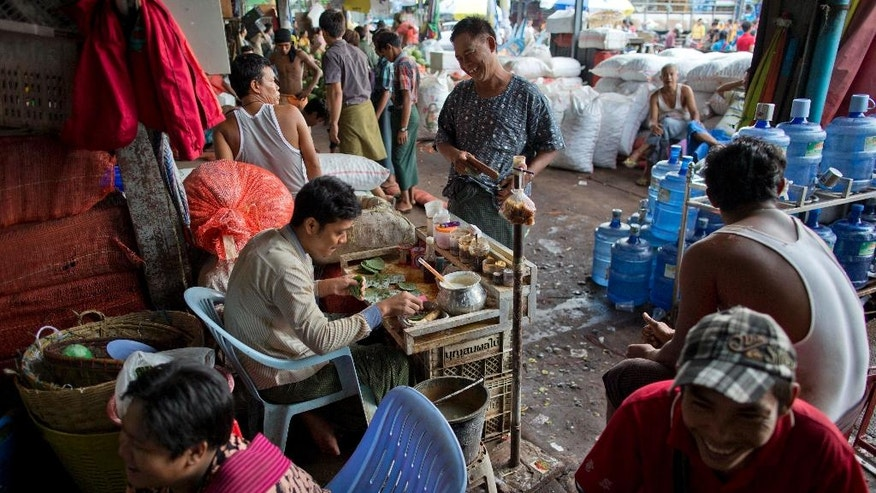 """In this Friday, June 3, 2016 photo, people gather around a """" kun-ya"""" seller at a market in Yangon, Myanmar. The bright green betel leaves, as large as an adult palm, normally cost $1.8 to $2.5 per kilogram (2.2 pounds). But because of a shortage the price has gone up nearly four times to 11,000 kyat or $9 per kilogram. (AP Photo/Gemunu Amarasinghe)"""