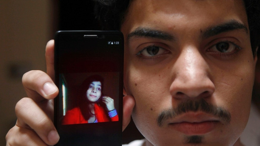 June 8, 2016: Hassan Khan shows the picture of his wife Zeenat Rafiq, who was burned alive, allegedly by her mother, on a mobile phone at his home in Lahore, Pakistan.