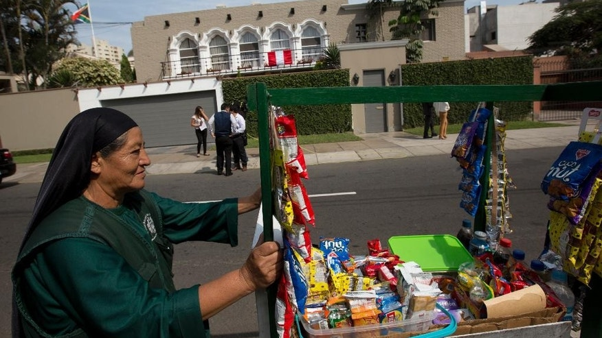 A street vendor pushes her cart of snacks past the home of presidential candidate Pedro Pablo Kuczynski where journalists are gathered in Lima, Peru, Wednesday, June 8, 2016. Economist Pedro Pablo Kuczynski clung to a thin lead over the daughter of a jailed former president early Wednesday as the count from Peru's presidential election dragged on, straining nerves in a nation divided after a polarizing campaign. (AP Photo/Silvia Izquierdo)