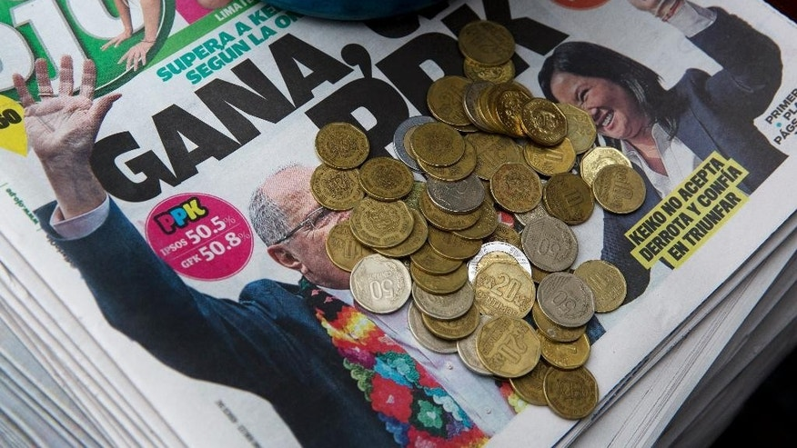 "Coins are collected atop a stack of newspapers with a headline that reads in Spanish; ""PPK Wins"", referring to presidential candidate Pedro Pablo Kuczynski,  in Lima, Peru, Monday, June 6, 2016. Early exit polls show presidential candidate Pedro Pablo Kuczynski with a slight lead over his rival Keiko Fujimori in Peru's runoff presidential election. (AP Photo/Rodrigo Abd)"