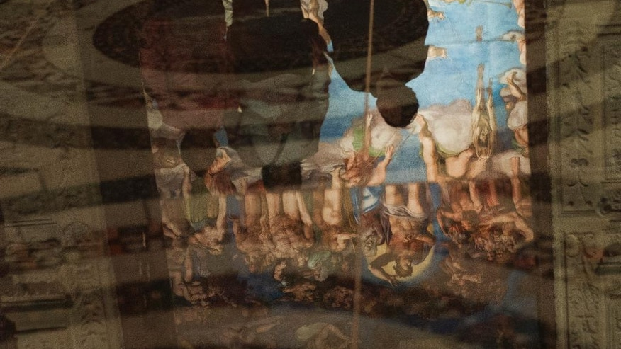 Visitors are reflected on the floor of a replica of the Sistine Chapel in Mexico City, Thursday, June 9, 2016. The Vatican granted permission for the construction of the life-size model that required millions of photographs to be made of the actual building. (AP Photo/Nick Wagner)