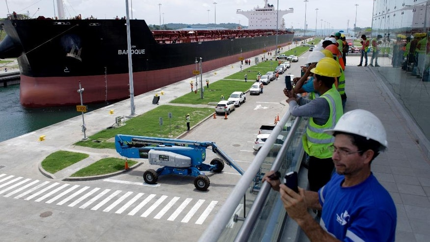 Workers take photographs of the Malta flagged cargo ship named Baroque, a post-Panamax vessel, as it navigates the Agua Clara locks during the first test of the newly expanded Panama Canal in Agua Clara, Panama, Thursday, June 9, 2016. The canal's expansion project will be inaugurated on June 26. (AP Photo/Arnulfo Franco)