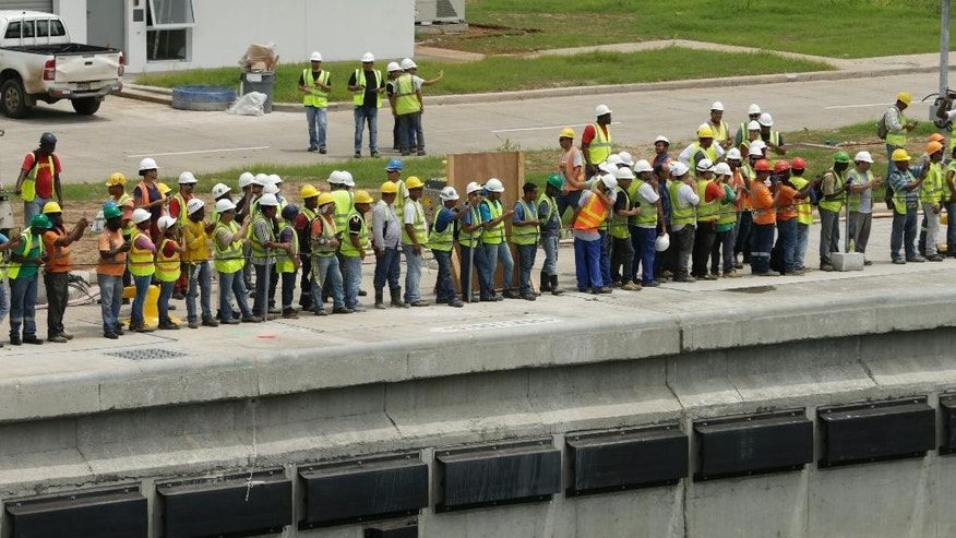 Panama Canal workers watch the Malta flagged cargo ship named Baroque, a Post-Panamax vessel, navigate the Agua Clara locks during the first test of the newly expanded Panama Canal, in Agua Clara, Panama, Thursday, June 9, 2016. The canal's expansion project will be officially inaugurated on June 26. (AP Photo/Arnulfo Franco)