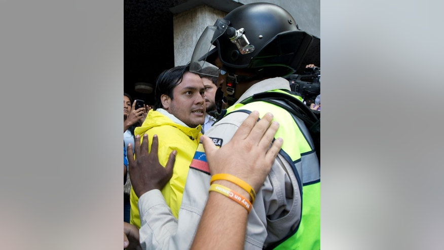 An opposition protester argues with a Bolivarian National Police officer as he and other protesters try to enter to the National Electoral Council, CNE, headquarters in Caracas, Venezuela, Thursday, June 9, 2016. Opposition members were turned back from the headquarters of Venezuela's electoral body where the group attempted to enter to demand the government allow it to pursue a recall referendum against President Nicolas Maduro. (AP Photo/Ariana Cubillos)