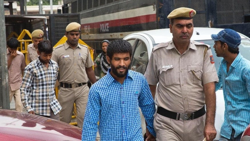 In this Thursday, June 9, 2016, photo, three of the five convicts in the gang rape of a 51-year-old Danish tourist in 2014, are escorted by the police for a hearing at a city court, in New Delhi, India. Five Indians who raped a Danish tourist when she asked them for directions in New Delhi have been sentenced to life in prison for the attack that highlighted the plague of sexual violence in the country. (AP Photo/Manish Swarup)