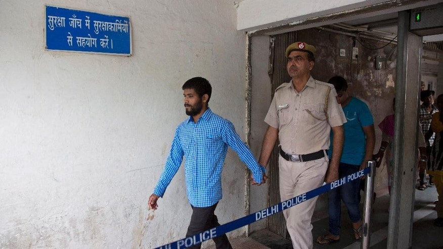 In this Thursday, June 9, 2016, photo, one of the five convicts in the gang rape of a 51-year-old Danish tourist in 2014, is escorted by the police for a hearing at a city court, in New Delhi, India. Five Indians who raped a Danish tourist when she asked them for directions in New Delhi have been sentenced to life in prison for the attack that highlighted the plague of sexual violence in the country. (AP Photo/Manish Swarup)