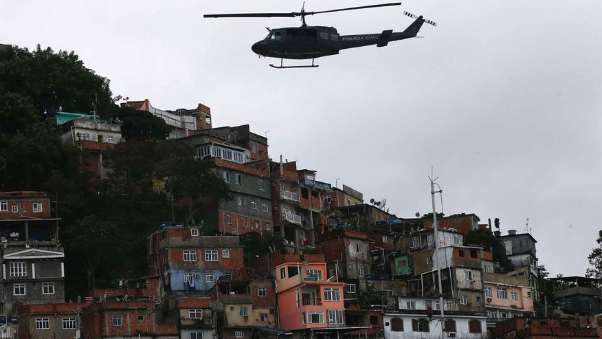 A Civil Police helicopter patrols over the Pavao-Pavaozinho favela on June 3, 2014 in Rio de Janeiro, Brazil.