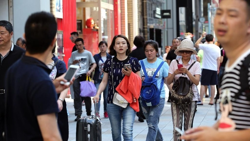 Chinese tourists walk around the Ginza shopping district in Tokyo, Friday, June 10, 2016.  As Japan steps up its efforts to attract overseas tourists, the number of visas issued hit a record high in 2015. Not all foreign nationals require visas to enter Japan, but data from the Ministry of Foreign Affairs reflect the overall growth in tourism and the sharp rise in travelers from China. (AP Photo/Koji Sasahara)