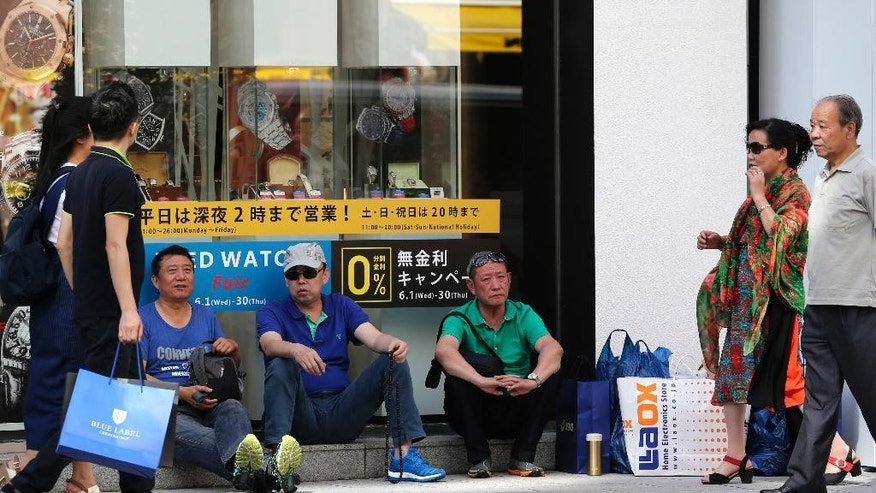 Chinese tourists rest on the ground at the Ginza shopping district in Tokyo, Friday, June 10, 2016. As Japan steps up its efforts to attract overseas tourists, the number of visas issued hit a record high in 2015. Not all foreign nationals require visas to enter Japan, but data from the Ministry of Foreign Affairs reflect the overall growth in tourism and the sharp rise in travelers from China. (AP Photo/Koji Sasahara)