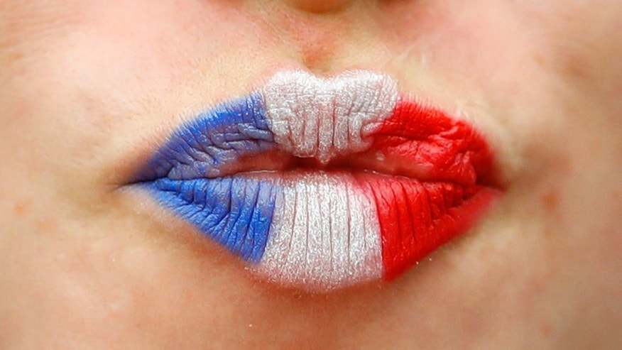 The lips of a French supporter are painted in the colors of the national flag, prior to the Euro 2016 Group A soccer match between France and Romania, at the Stade de France, in Saint-Denis, north of Paris, Friday, June 10, 2016. (AP Photo/Frank Augstein)