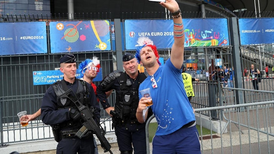 France supporters take a selfie with French police officers outside the stadium before the Euro 2016 Group A soccer match between France and Romania, at the Stade de France, in Saint-Denis, north of Paris, Friday, June 10, 2016. (AP Photo/Thibault Camus)