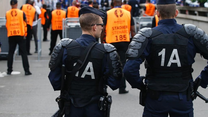 French police officers and stewards watch closely as fans gather before security checks at the Stade de France stadium in Saint Denis, north of Paris, France, prior to the Euro 2016 Group A soccer match between France and Romania, Friday, June 10, 2016.  (AP Photo/Darko Vojinovic)