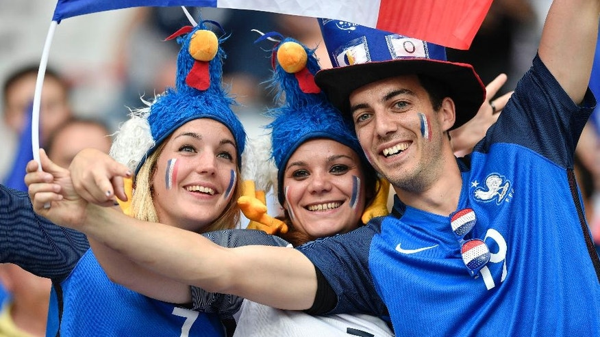 Supporters of France pose for photos on the stands before the Euro 2016 Group A soccer match between France and Romania, at the Stade de France, in Saint-Denis, north of Paris, Friday, June 10, 2016. (AP Photo/Martin Meissner)