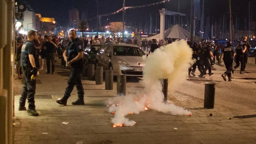 Teargas smokes as police and soccer fans gather in downtown Marseille, France, early Friday, June 10, 2016. Trouble flared outside an Irish pub in the Old Port of the southern city just before midnight Thursday, apparently between English fans drinking there and some local people. Marseille is hosting a European Championship soccer match between England and Russia on Saturday. (AP Photo/Darko Bandic)