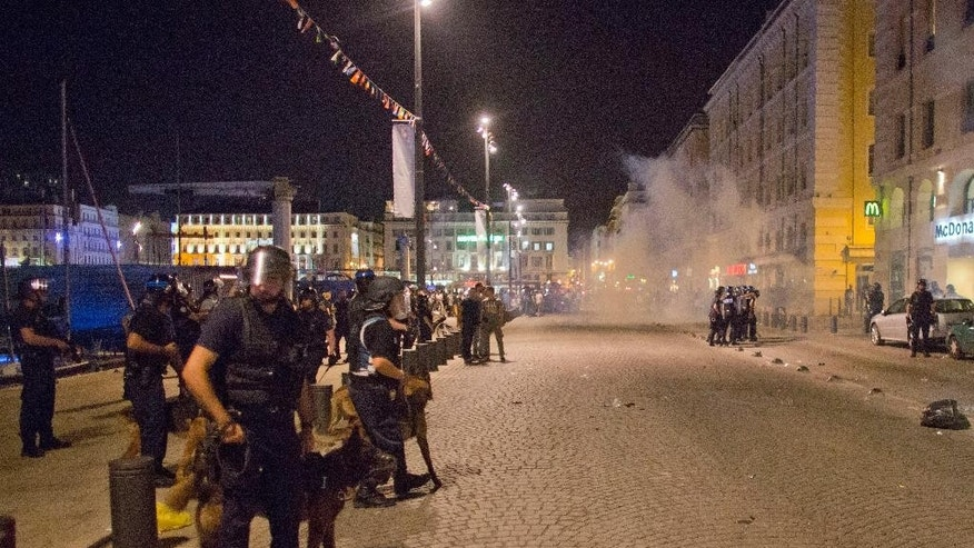 Teargas fills the air as police and soccer fans gather in downtown Marseille, France, early Friday, June 10, 2016. Trouble flared outside an Irish pub in the Old Port of the southern city just before midnight Thursday, apparently between English fans drinking there and some local people. Marseille is hosting a European Championship soccer match between England and Russia on Saturday. (AP Photo/Darko Bandic)